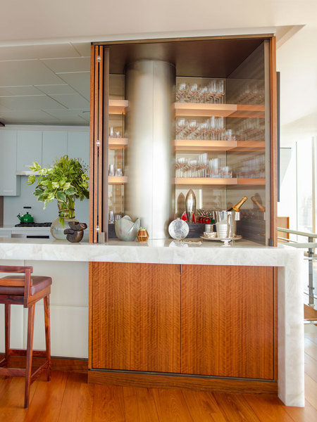 A stately wood bar cabinet designed by Phillip Thomas is a refined addition to a kitchen counter area