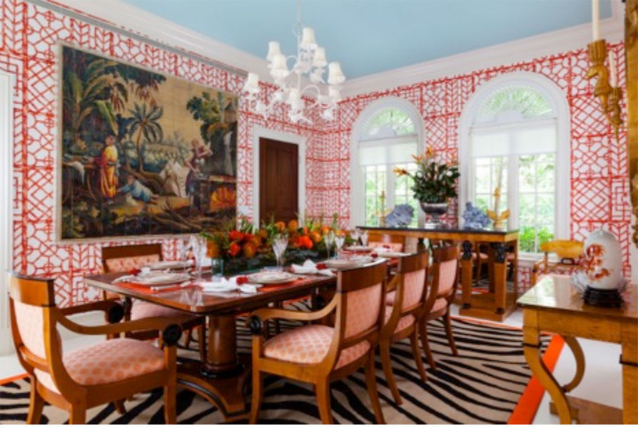 Red-patterned wallpaper in this dining room designed by Palm Beach, Florida-based designer Carleton V