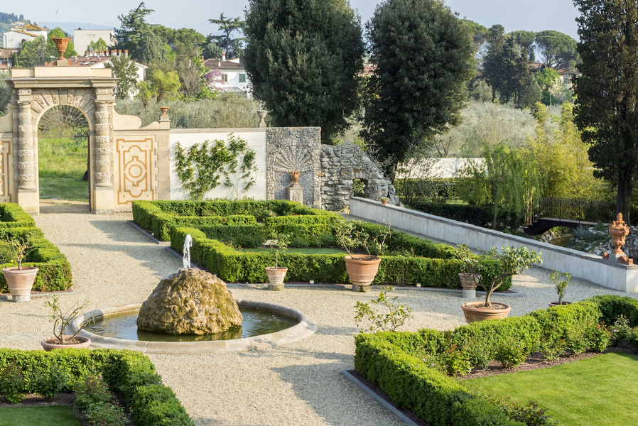 The formal gardens feature stone statues and clipped box hedging