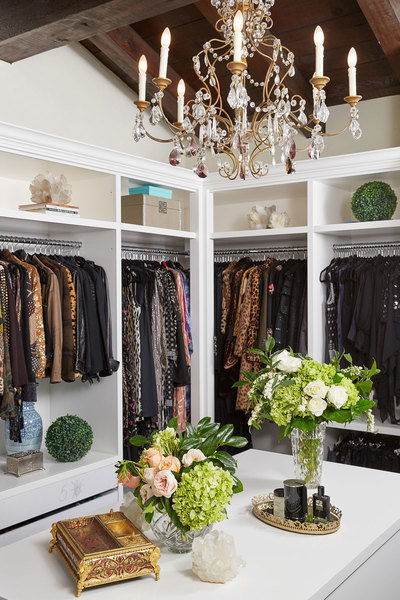 Detalles personalizados, como jarrones de flores, cajas de joyas y una araña hacen que este vestidor