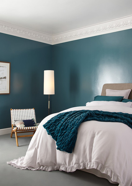 As this bedroom proves, a dark paint can add lightness to the room when it has a glossy finish, which