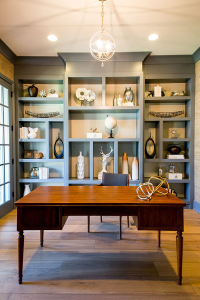 A standout wall unit with built-in storage and a statement wood desk create an eclectic feel in this