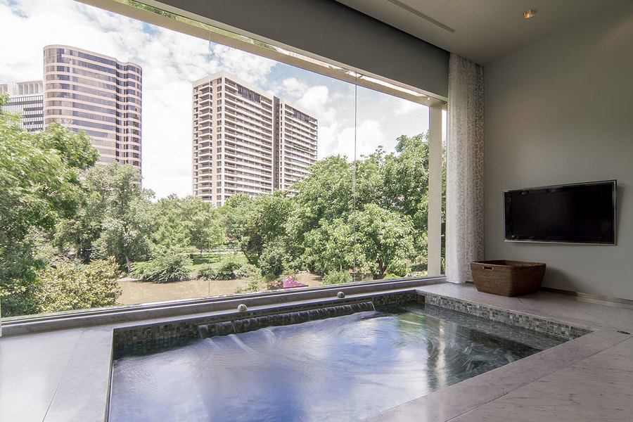 The master suite's jetted tub offers views of the city, or anything else via the adjoining flatscreen