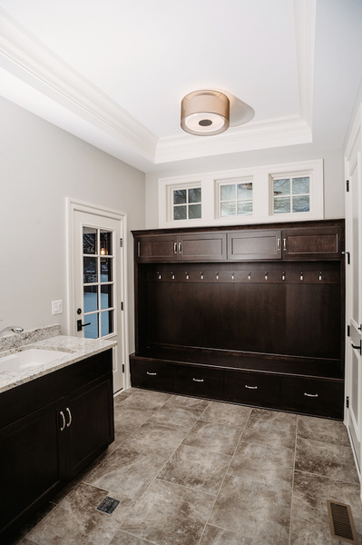 Elements like marble-like tiling and wood cabinetry elevate this mudroom designed by Donna Mondi.