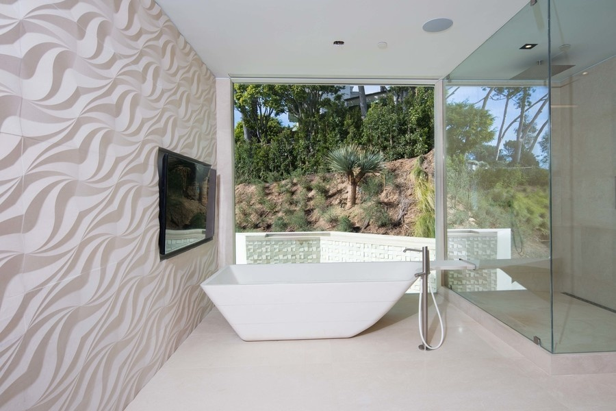 """This Porcelanosa tub in the """"her"""" master bathroom cost $60,000."""