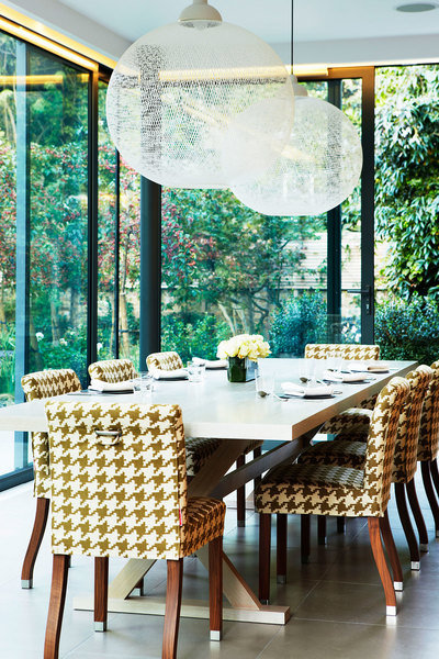A glass-enclosed West London terrace designed by Karen Howes lets the surrounding landscaping take ce
